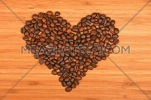 Heart shaped coffee beans of Roasted Arabica espresso beans over wooden bamboo board background