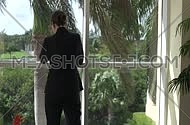 Medium shot for a male business woman wearing suit and Talking in her smartphone at day.