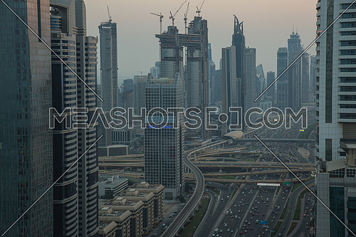 Long shot for Dubai City showing skyscrapers and traffic at sunset.