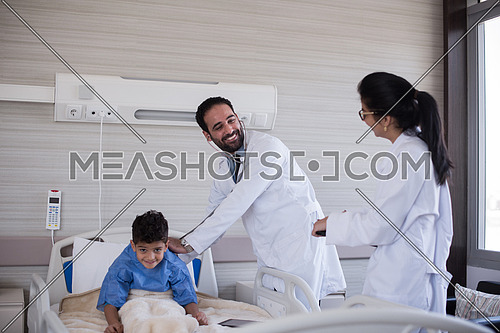 arabian mischievous and beauty kid get treatment by young doctors in modern hospital room