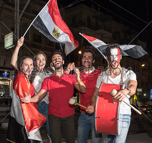 group of young people cheering for egypt, holding egyptian flags and drum while one of them has a paint egyptian flag on his face in the korba area at night