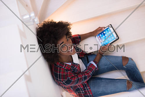 Attractive young black woman using her electronic tablet while sitting on a staircase