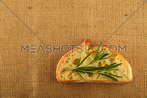 Jute canvas with rosemary leaves on slice of white wheat bread, add your text