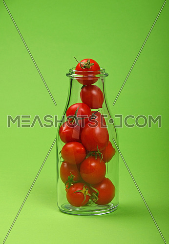 Big glass bottle full of red cherry tomatoes over green background as symbol of fresh natural organic juice or ketchup