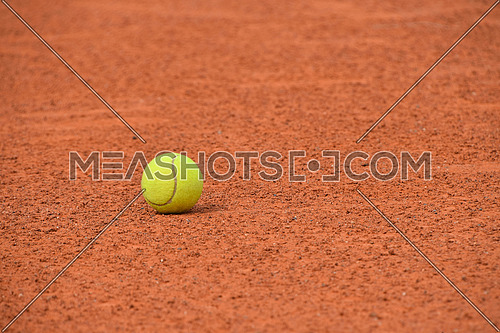 Close up one yellow felt tennis ball on red brown clay ground court, low angle view