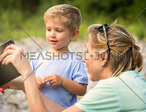 Mom shows her mobil phone to the child who looks surprised, sunny day, horizontal photo close up.