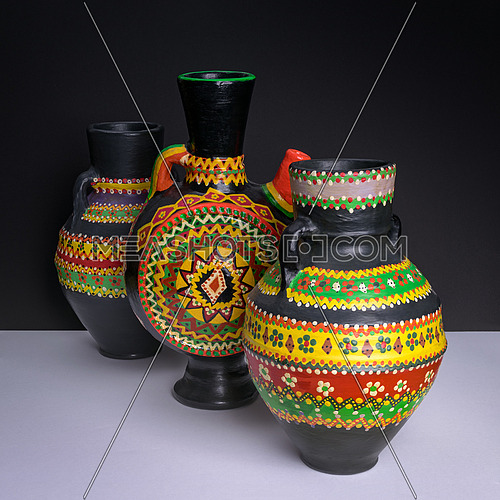 Still life of three black decorated colorful handcrafted pottery jugs