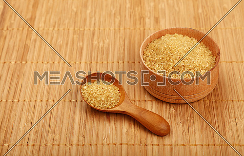 Wooden round scoop spoon and small bowl of brown cane sugar on bamboo mat background