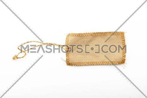Blank canvas label tag overlocked with jute rope and metal rivet isolated on white