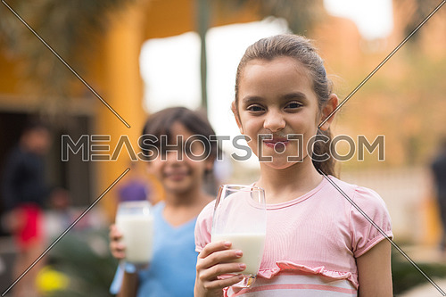 Middle Eastern girl enjoying with a glass of milk in his hand outside on summer day