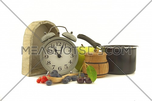 Culinary still life with old-fashioned alarm clock, pot, apple, jar of honey, cherries, red currants and blueberries over an off white background with copy space