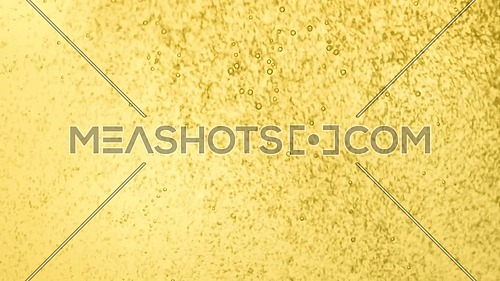 Close up background of pouring yellow lemonade sparkling soda water with gas in full transparent glass, low angle side view, slow motion