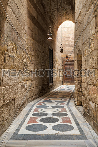 Arched corridor leading to the courtyard of Sultan Barquq mosque with stone bricks wall, ornate colored marble floor and wooden door, Old Cairo, Egypt