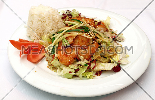 Roasted king shrimps prawns with steamed rice and fresh vegetable salad on white plate, the meal of Chinese cuisine, close up, high angle view, personal perspective
