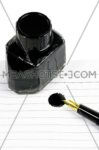classic black fountain pen on open notebook with ink bottle with stain on page