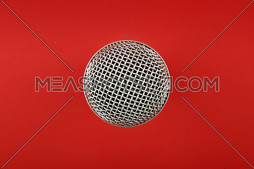 Microphone top view over red background, close up, personal perspective