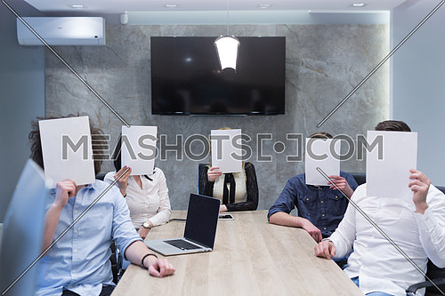 Portrait of a young business team holding a white paper over their face  in the startup office