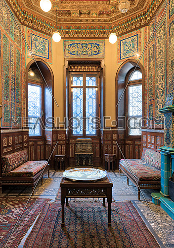 Manial Palace of Prince Mohammed Ali. Winter room at the Residence Hall, with ornate wall and ceiling, windows, decorated couches, tea tables and ornate carpet
