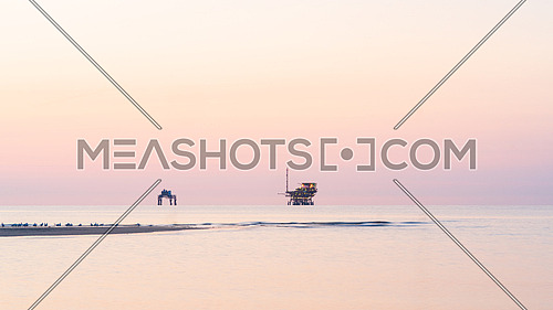 Platforms for extraction and transformation of natural gas at sunrise, Adriatic sea, ravenna, italy.