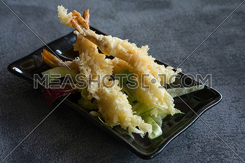 Japanese Cuisine - Tempura Shrimps (Deep Fried Shrimps) with sauce and vegetables on a black plate. Gray background,shallow depth of field