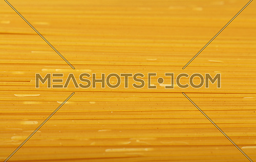 Close up background pattern of dry uncooked spaghetti pasta, high angle view, selective focus