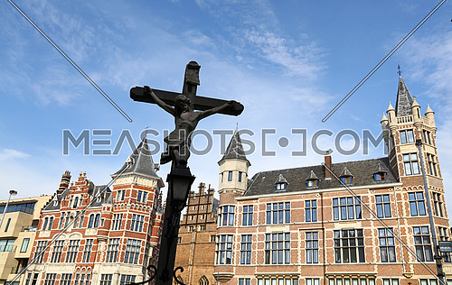 Low angle view of cross rood over old historical buildings and clear blue sky of Antwerp, Belgium