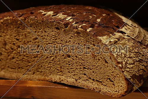 Half of artisan dark black fresh rye bread loaf cut on wooden board, close up, low angle view