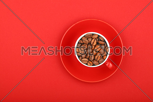 One small red espresso cup full of roasted coffee beans, with saucer on red paper background, top view, bird eye view
