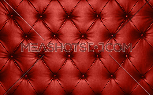 Close up background texture of scarlet red capitone genuine leather, retro Chesterfield style soft tufted furniture upholstery with deep diamond pattern and buttons