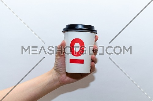 female holding a take away paper cup of Espressolab / Espresso Lab with it's black cap and red logo; December 2018 in Cairo - Egypt