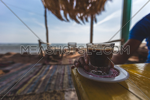 Close up for male hand holding coffee glass by the beach in Dahab, Egypt