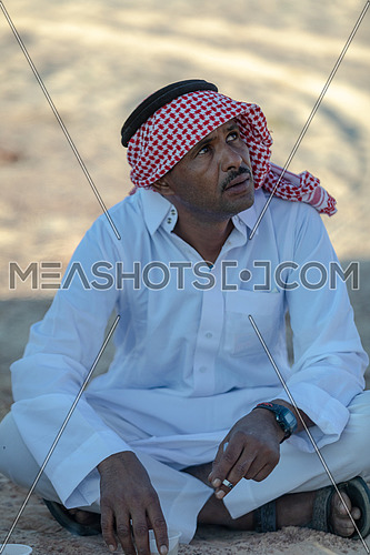 Portirat for a bediuon male wearing traditional clothing and smoke cigarettes in Sinai at day.