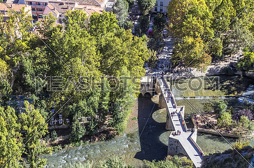 Alcala del Jucar, Spain - October 29, 2016: Roman bridge, located in the central part of the town, to its passage by the river Jucar, at the top of mountain limestone is situated castle of Almohad origin of the century XII, Alcala del Jucar, Spain