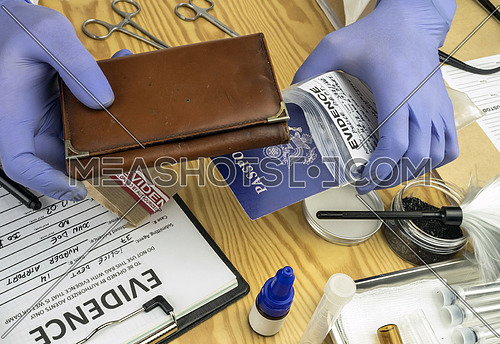 Police expert examining American passport and purse of a evidence bag in criminalistic laboratory, conceptual image