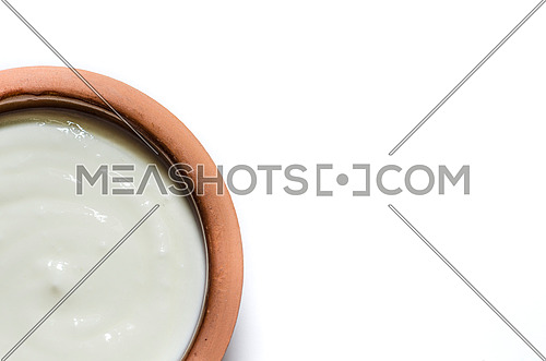 Close up on a pottery rounded plate filled with yogurt