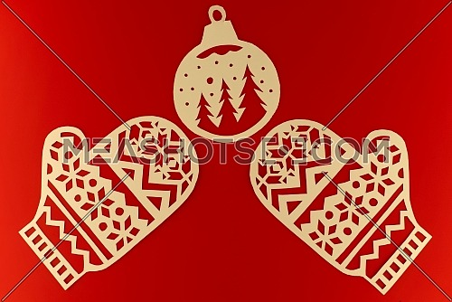New Year and Christmas flat lay on festive red background with paper cut gloves and ball ornament with copy space for text