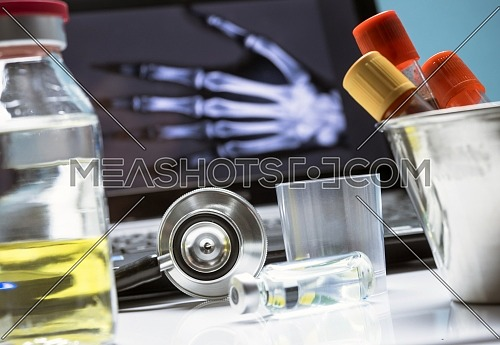 Several vials and blood sample next to stethoscope in a hospital, conceptual image