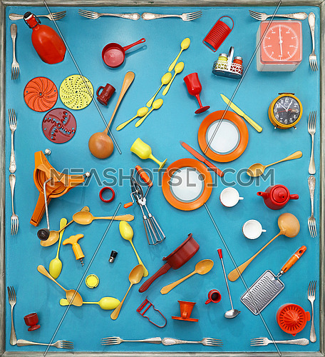Close up flat lay of different colorful multicolor painted kitchen utensils and tools, plates, spoons, forks, knives, cups, teapot, elevated top view, directly above