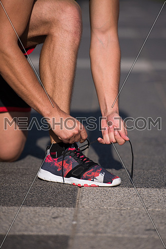 Sport exercise, fitness, workout. Young athlete, runner tie shoelaces in shoes. Outdoor activity, endurance. Active person road training. Healthy lifestyle.