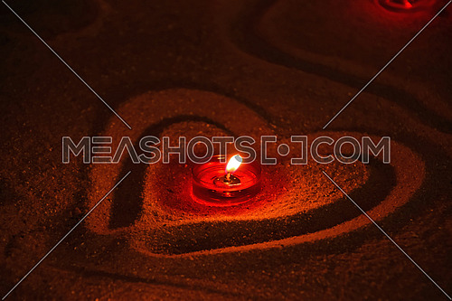 Red church tea candle burning in heart shaped sand, close up, high angle view