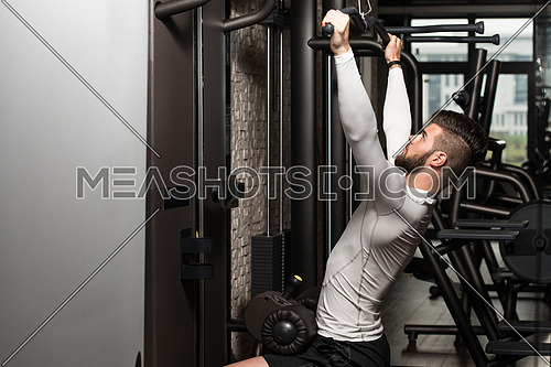 Young Man Doing Heavy Weight Exercise For Back In Gym