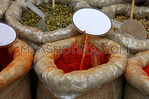 Close up several canvas bags of assorted spices, red paprika and green pepper,  with copy space of blank price tags on retail display of market stall, high angle view