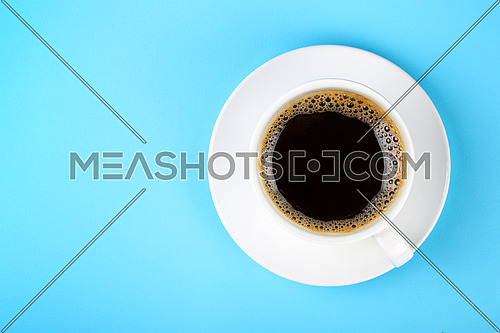 Close up one full white cup of black Americano coffee and saucer over pastel blue paper background, elevated top view, directly above
