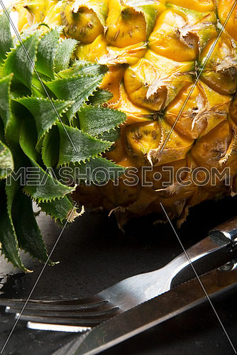 ripe pineapple on a black plate with knife and fork