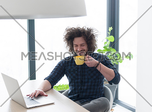 young man drinking coffee while working from home on his laptop computer