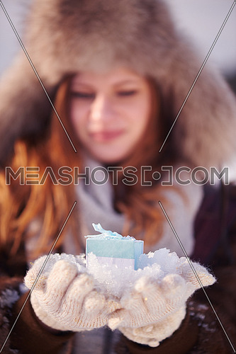 happy young redhair girl  with gift and snow in  hands. Christmas and winter shopping.
