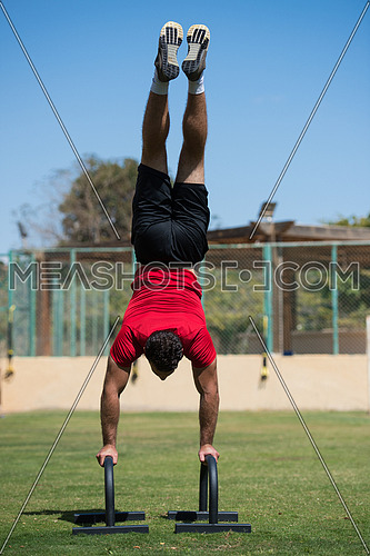 young middle eastern athletic man workout handstand outside on a sunny day