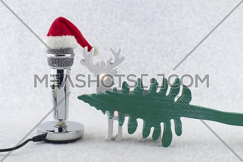 Microphone with Santa hat and Christmas decorations on a snowy white background, space for text. Christmas carol concept