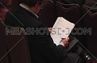 Medium shot from behind for a male business man Skimming papers at a meeting.