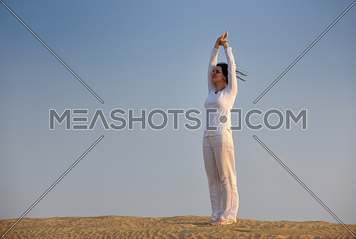 happy young woman relax and exercise yoga at desert in sunset